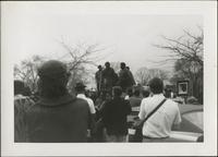 Crowd looking toward group of African American men wearing berets and speaking into microphone