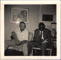 Leon Jordan sitting with unidentified man taking notes