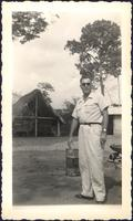 unidentified man standing by a barrel