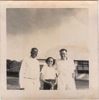 Two unidentified men and a woman in front of a building