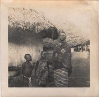 Two unidentified children and a woman in front of huts