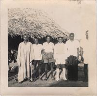 Six unidentified men in front of a hut