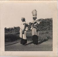 Two unidentified women standing back to back