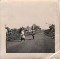 Two unidentified women walking down an open road