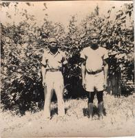 Two young men in an open patch of grass