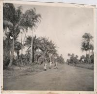 Three unidentified people walking down a dirt road