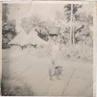 unidentified woman walking down an open dirt road