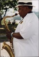 Ahmad Alaadeen playing a saxophone outdoors