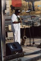 Ahmad Alaadeen playing soprano saxophone while standing on an outdoor stage