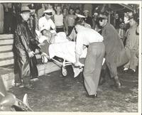 Dave Dexter assisting medical personnel with a man on a gurney