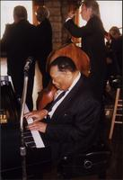Jay McShann with Ahmad Alaadeen, Al Pearson, Gerald Spaits, and Terry Hughes performing in a sunny room