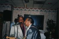 Ahmad Alaadeen and Sonny Kenner share a microphone to sing together