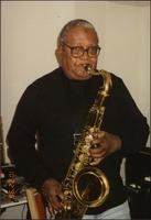 Ahmad Alaadeen stands to practice his tenor saxophone