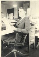 L. Perry Cookingham seated at desk