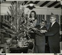 Patricia Stevens, G. Jerry Garafolo, and Joseph Netahla, decorating a Christmas tree for a charity benefit picnic
