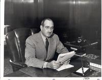 L. Perry Cookingham at desk with papers in hand