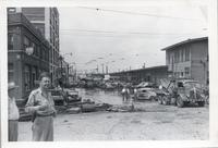 Police Officer standing on street while workers clear it of flood damage, 1951 flood