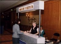 Woman signing in at the registration desk