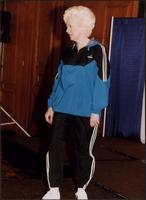 Older woman modeling a track suit during a fashion show at the Women's Expo