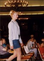 Model in denim shorts and plaid shirt during a fashion show at the Women's Expo