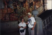 Two unidentified tourists standing in front of a mural
