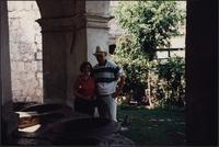 Two unidentified tourists standing in front of an archway