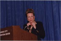 Melissa Stevens speaks from a podium during the Boat Show Fashion Show