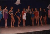 Ten Stevens models stand in a line in one-piece swimsuits with a male model in fishing gear during the Boat Show Fashion Show