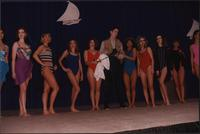 Ten Stevens models stand in a line in swimsuits with a male model in fishing gear during the Boat Show Fashion Show