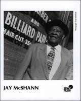 Publicity photo of Jay McShann in front of a barber shop and billiards parlor