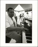 Jay McShann playing piano under a tent