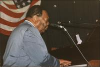 Jay McShann playing piano with flag in the background