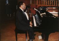 Jay McShann seated at a piano and speaking