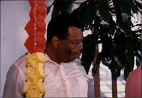 Jay McShann near a potted tree and artificial lei