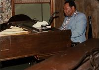 Jay McShann playing piano in a light blue suit