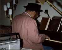 Jay McShann playing piano and wearing a hat