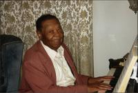 Jay McShann playing piano and smiling at the camera