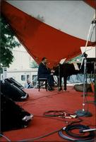 Jay McShann playing piano under a red and white awning
