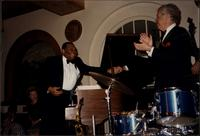 Jay McShann shaking hands with someone while Bobby Rosengarden applauds