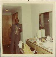 Unidentified man holding a drink in a hotel room