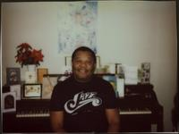 Jay McShann at his piano in a t-shirt