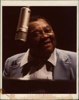 Jay McShann playing piano with microphone in front of him