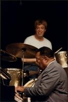 Jay McShann playing piano on stage with Butch Miles behind him