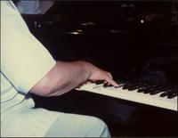 Close up of Jay McShann's arm and hand playing piano