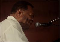 Close up of Jay McShann playing piano and singing in Japan