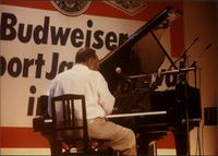 View of Jay McShann from behind playing piano in Japan
