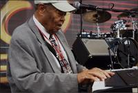 Close up of Jay McShann playing an electronic piano and singing