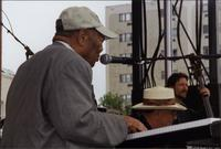 Jay McShann, Duke Robillard, and unidentified bassist performing outdoors