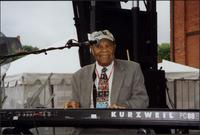 Jay McShann playing an electronic piano and smiling