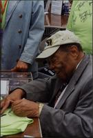 Close up of Jay McShann signing autographs